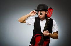 Bärande solglasögon för man och spelagitarr Royaltyfri Bild