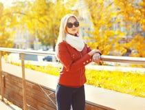 Bärande solglasögon för nätt blond kvinna och rött omslag med halsduken i solig höst royaltyfri bild