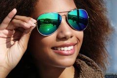 Bärande solglasögon för nätt kvinna med perfekta tänder och mörk ren hud som har att vila utomhus arkivbild