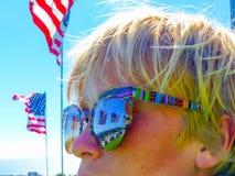 Bärande solglasögon för patriotisk Kalifornien pojke som förbiser den Malibu stranden Arkivfoton