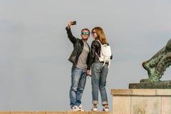 Bärande solglasögon för unga caucasian turist- par som står på höjdpunktjordning som tar en selfie Arkivfoton