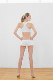Bärande sportswear för attraktiv spenslig kvinna som poserar att stå i sportkorridor Royaltyfri Foto