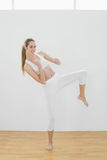 Bärande sportswear för gullig kvinna som gör kampsporter i sportkorridor Arkivfoton