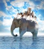 Bärande stad för elefant på baksida med moln Royaltyfri Bild