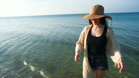 Bärande sugrörhatt för ung kvinna som tycker om och dansar vid havet arkivfilmer
