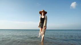 Bärande sugrörhatt för ung kvinna som tycker om och dansar vid havet lager videofilmer