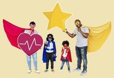 Bärande superherodräkter för lycklig familj arkivbild