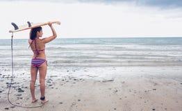 Bärande surfingbräda för bikinikvinna på huvudet på stranden Arkivbilder