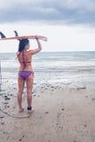Bärande surfingbräda för bikinikvinna på huvudet på stranden Arkivfoto