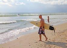 BÄRANDE SURFINGBRÄDA FÖR MAN Royaltyfri Bild