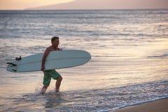 Bärande surfingbräda ut ur vatten Arkivfoton