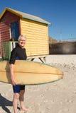 Bärande surfingbrädaanseende för hög man mot strandkoja Royaltyfri Fotografi