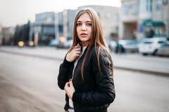 Bärande t-skjorta för modeflicka och läderomslag som poserar mot gatan, stads- bekläda stil arkivfoto