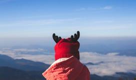 Bärande tröja för gullig asiatisk barnflicka och varm hatt som ser till den härliga mist- och bergnaturen i vinter fotografering för bildbyråer