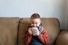 Bärande tröja för ung pojke och en halsduk som sitter på en soffa och dricker varmt te med citronen Influensa och säsongsbetonade arkivbilder