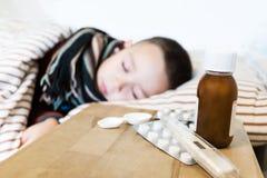 Bärande tröja för ung pojke och en halsduk som sover i hans säng, medan ha en influensa Meds och syrips på en trätabell framme fotografering för bildbyråer