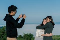 3 bärande tröjor för asiatisk vängrupp, tar en selfietelefon, område bak dimman och berg med ett le uttryck arkivfoto