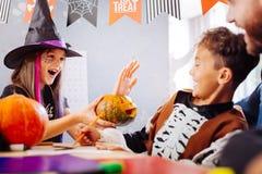 bärande trollkarlhatt för Mörker-haired syster som spelar trick med hennes broder arkivfoto