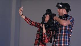 Bärande virtuell verklighetexponeringsglas och vapen för ung man som och för kvinna tar selfies på telefonen Arkivbilder