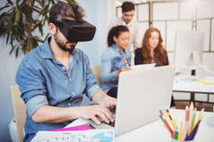 Bärande virtuell verklighethörlurar med mikrofon för affärsman, medan genom att använda bärbara datorn mot kollegor arkivbild