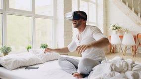 Bärande virtuell verklighethörlurar med mikrofon för ung gladlynt man som har video erfarenhet för 360 VR, medan sitta i säng hem fotografering för bildbyråer