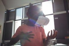 Bärande virtuell verklighetsimulator för pojke i klassrum arkivfoton