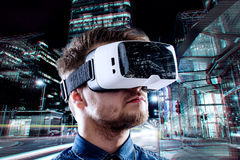 Bärande virtuell verklighetskyddsglasögon för man mot nattstad Arkivfoton