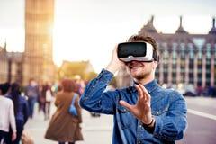 Bärande virtuell verklighetskyddsglasögon för man Westminster bro, London, Arkivbilder