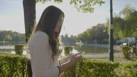 Bärande vit elegant kläder för härlig ung flicka som går och smsar från smartphonen i parkera i ultrarapid - stock video
