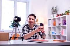 bärande vit hörlurar för Mörker-haired kompetent granskare och testa dem fotografering för bildbyråer