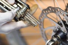 Bärande vit handske för Closeuphand som rymmer det mång- unbrakotangenthjälpmedlet bredvid delar av cykelhjulet, mekaniskt repara arkivbilder