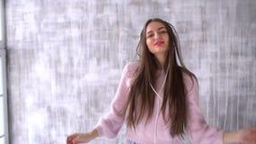 Bärande vit headphone för gullig kvinna och lyssna Dans med skratt och leende av nöje Slut upp inomhus brigham lager videofilmer