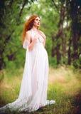 Bärande vit klänning för härlig ljust rödbrun kvinna i en trädgård fotografering för bildbyråer
