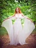 Bärande vit klänning för härlig rödhårig manälvakvinna i en trädgård Arkivbild