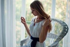 Bärande vit klänning för nätt brunett som poserar på soffan Fotografering för Bildbyråer