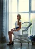 Bärande vit klänning för nätt brunett som poserar på soffan Arkivfoto