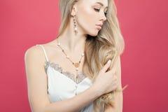 Bärande vit silkeslen överkant för perfekt blond kvinna och guld- smyckenörhänge och halsband på färgrik rosa bakgrund arkivfoto