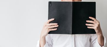 B?rande vit skjorta f?r man och rymma en svart r?kningsbok framme av honom p? r?tsidan med kopieringsutrymme arkivbilder