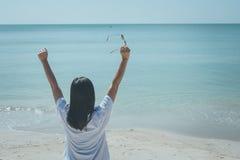 Bärande vit t-skjorta för kvinna, henne som står på sandstrand- och innehavsolglasögon i hennes hand, henne som ser havet och den royaltyfria foton