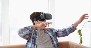 Bärande vrhörlurar med mikrofon för man och göra en gest på soffan lager videofilmer