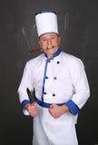 Bärande workwear och innehav för kock en kniv Fotografering för Bildbyråer