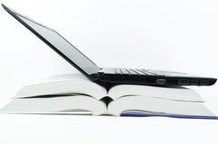 Bärbar dator över böcker Arkivbilder