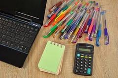 Bärbar dator anteckningsbok, färgpennor Arkivbild