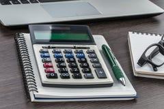 Bärbar dator, anteckningsbok och penna med räknemaskinen på skrivbordet Arkivbilder