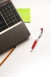 Bärbar dator, blyertspenna och penna Arkivbild