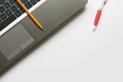 Bärbar dator, blyertspenna och penna Arkivbilder