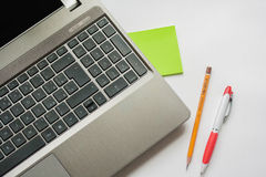 Bärbar dator, blyertspenna och penna Royaltyfri Bild