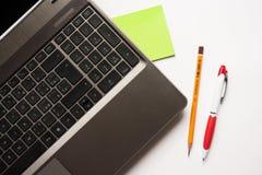 Bärbar dator, blyertspenna och penna Royaltyfri Foto