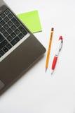 Bärbar dator, blyertspenna och penna Fotografering för Bildbyråer
