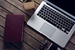 Bärbar dator-, dagbok-, anblick-, kamera- och pennhållare på trätabellen arkivbild